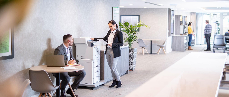 O femei imbracata in costum sta la un multifunctional MFC-L9570CDWTT, barbat in costum sta la o masa cu un laptop, planta, persoane in spate