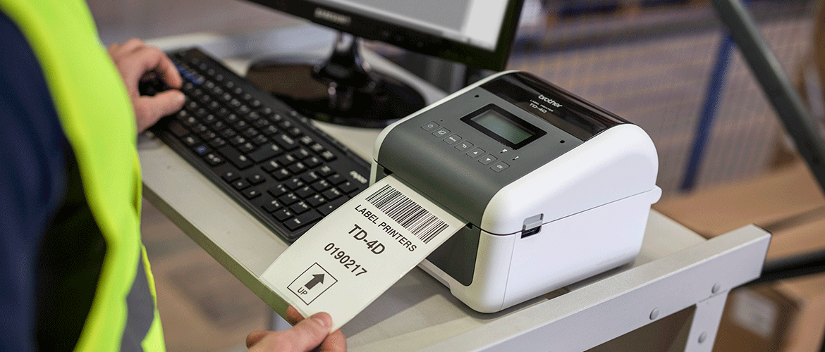 Man taking label from Brother TD-4D label printer on desk with computer monitor and keyboard