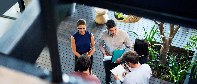 Colegi în spațiul de lucru al viitorului într-o întâlnire informală.