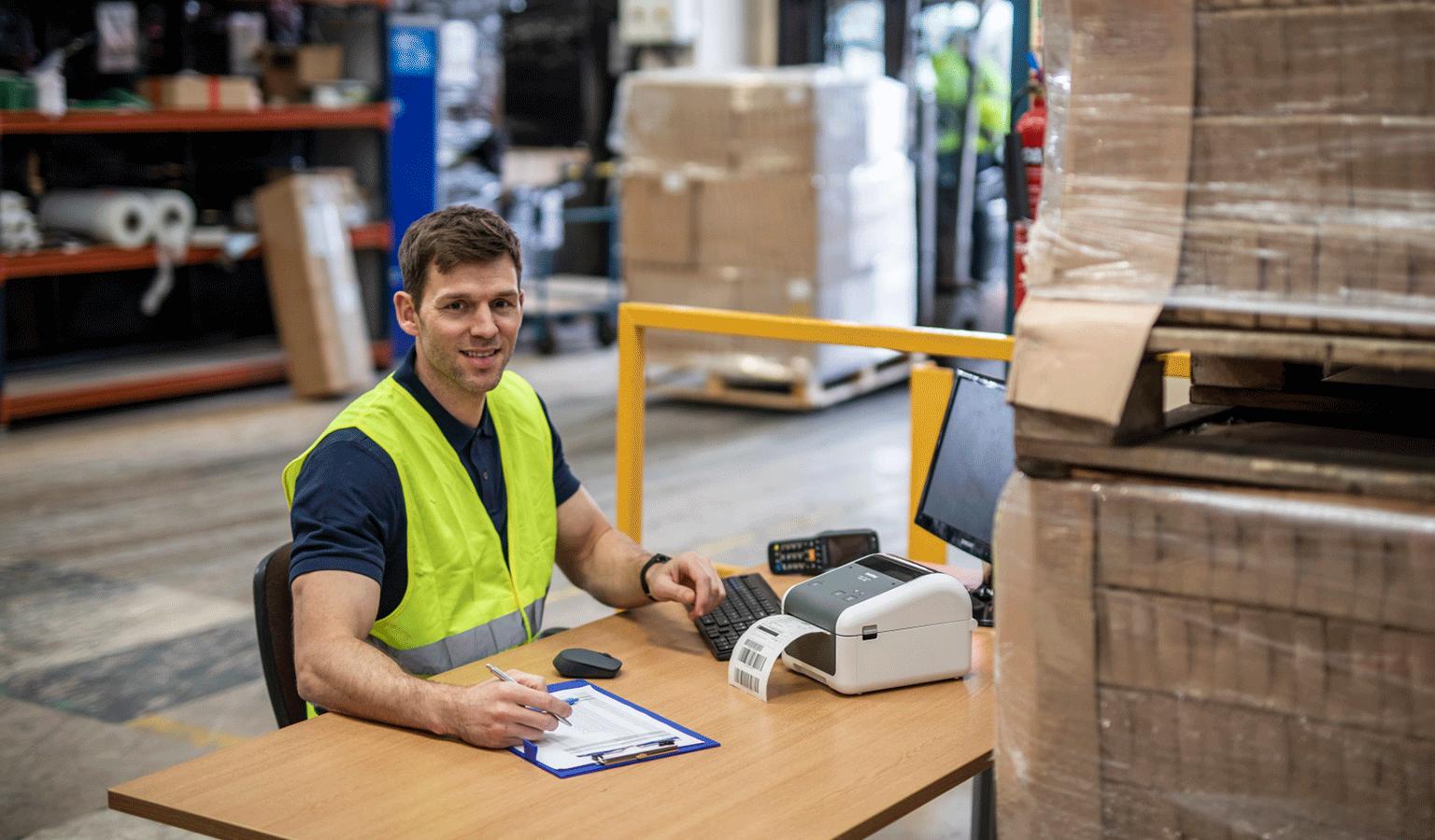 Bărbat care lucrează la birou cu imprimanta TD4D Brother într-un depozit