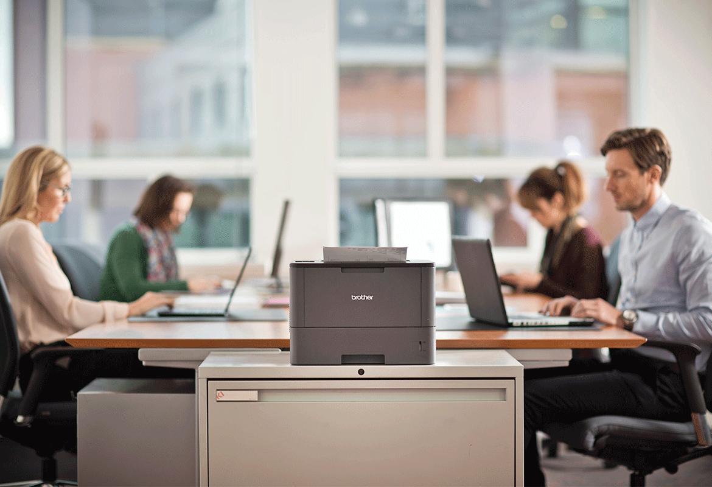 Imprimanta laser Brother sta pe un birou cu angajati in spate