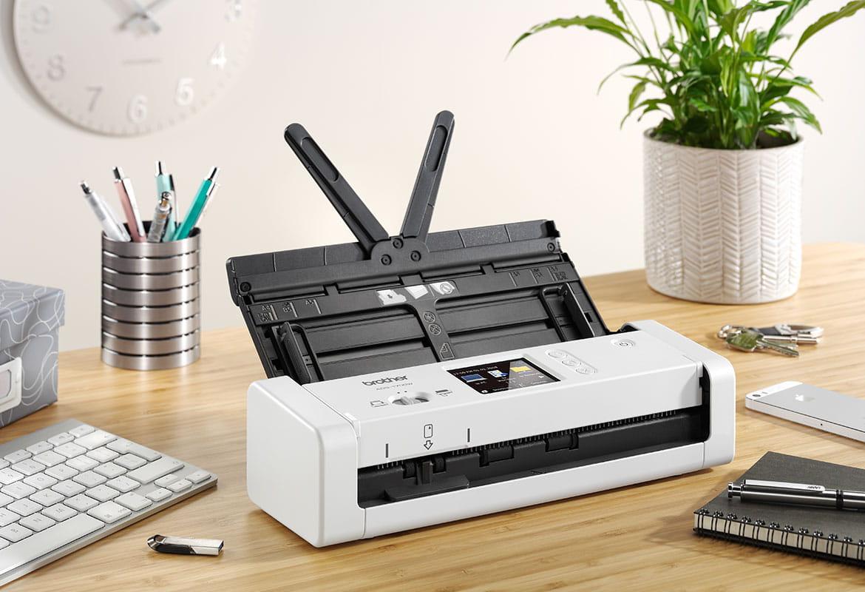 Scaner compact de document ADS-1700W pe un birou de lemn cu o planta si o tastatura