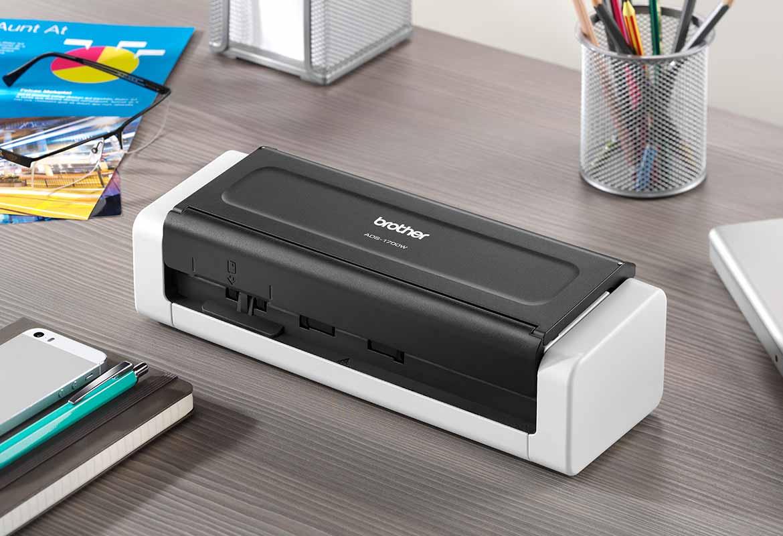 Scaner compact de documente ADS-1700W inchis pe un birou gri