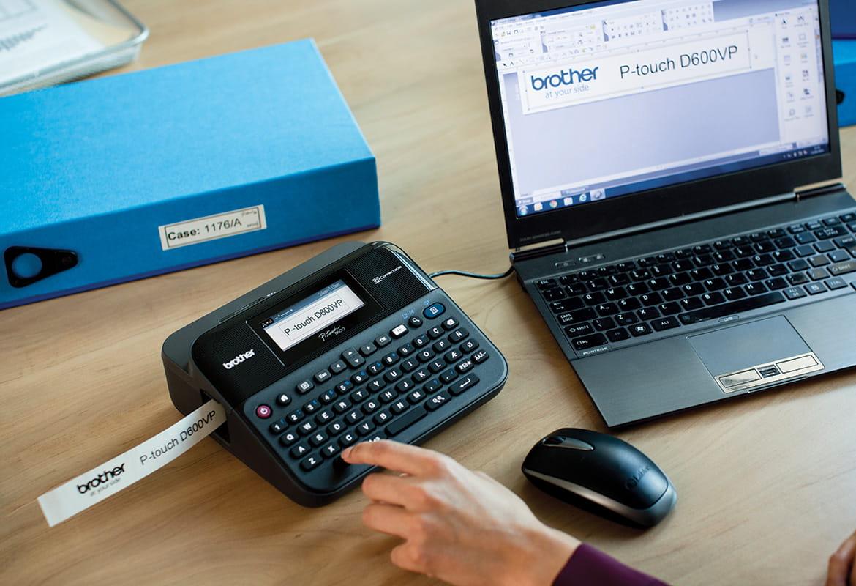 Imprimanta de etichete P-touch pe un birou, conectata la un laptop, cu o eticheta imprimata