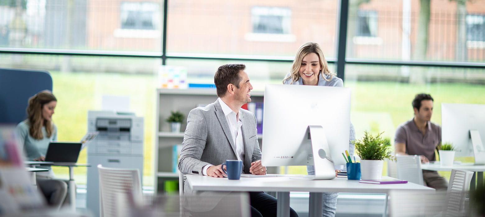 Angajat la birou discutand cu o colega, imprimantă Brother în fundal