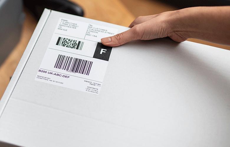Eticheta logistica alba lipita pe o cutie alba de o mana