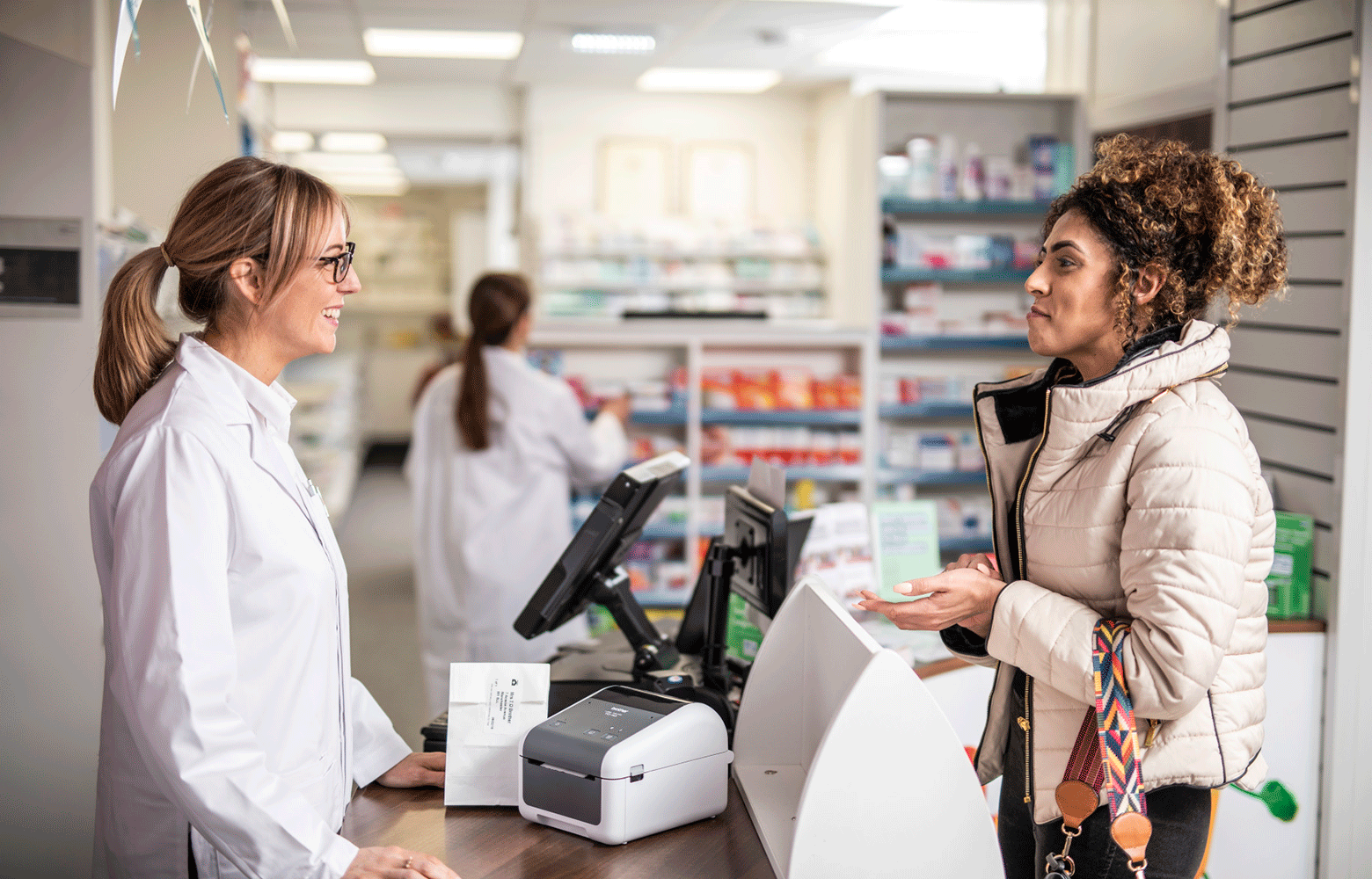 Farmacist discutand cu o clienta intr-o farmacie