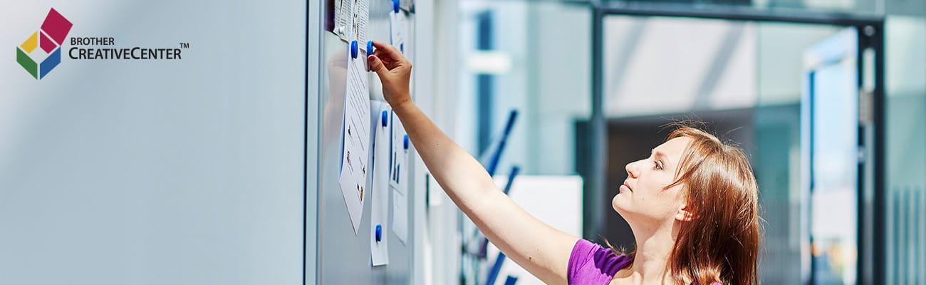 femeie fixând un anunț la birou