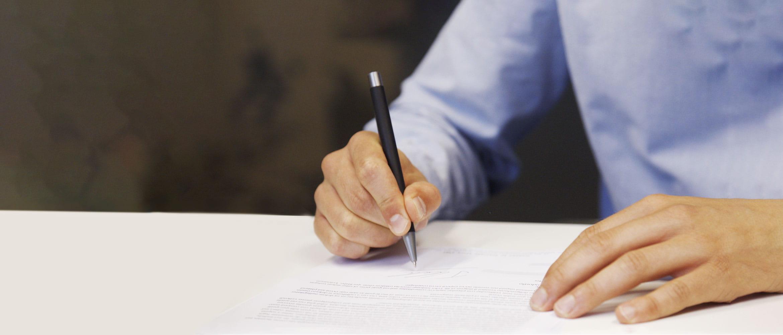 Barbat in camasa albastra semnand un document