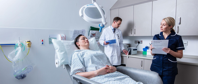 Pacientă la tratament cu doctor și asistentă completând un formular