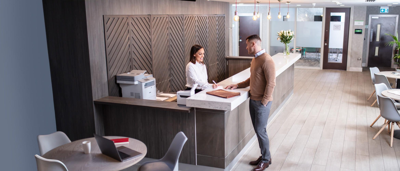 Angajată stând de vorbă cu client în hotel