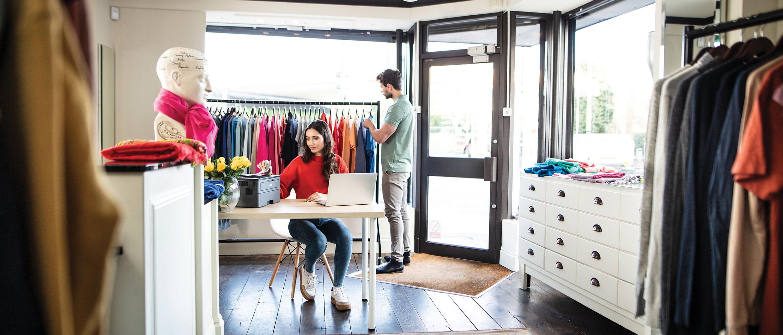 Bărbat la cumpărături și femeie la birou imprimând un document în magazin
