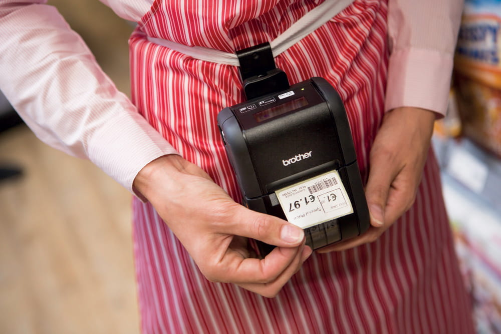 Brother RJ portable label printer with price label being printed