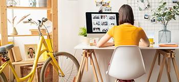 femeie la birou cu bicicletă galbenă alături