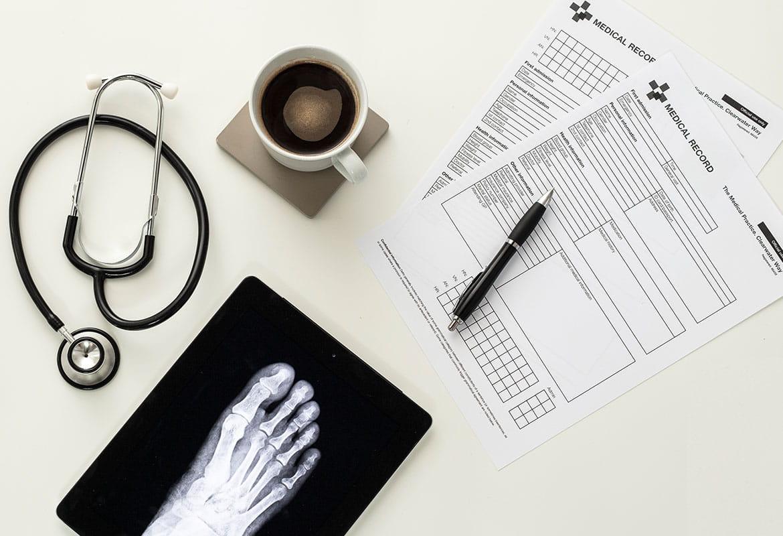 Fișe medicale, cană cu cafea, radiografie pe birou