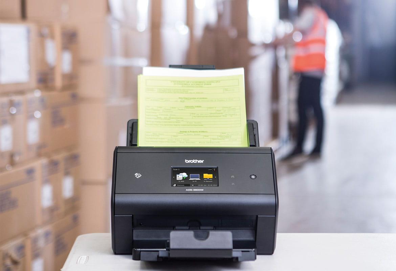 Scaner desktop Brother ADS-3600W pe birou arhivând note de livrare în depozit