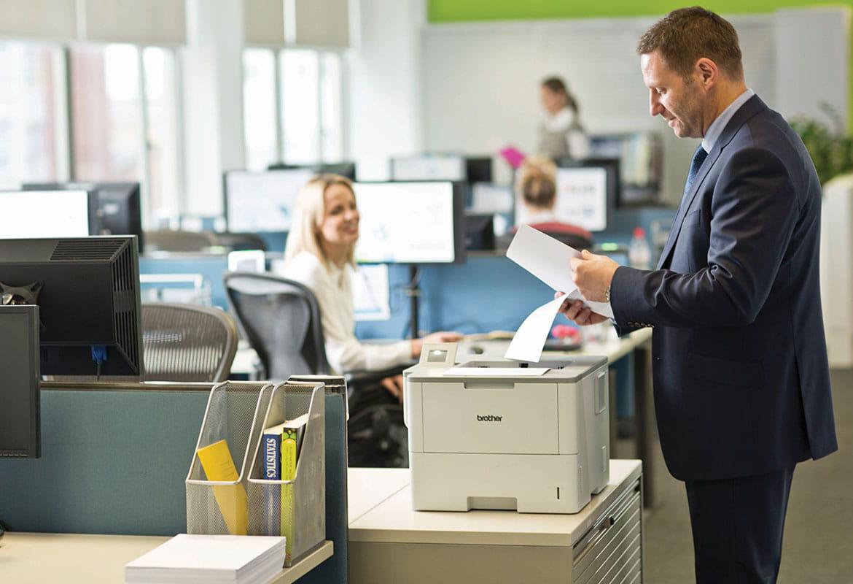 Angajat alături de imprimantă Brother ținând un document