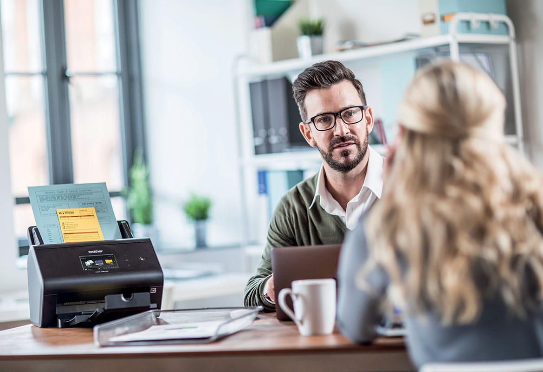 Angajat la birou împreună cu clientă și scaner Brother
