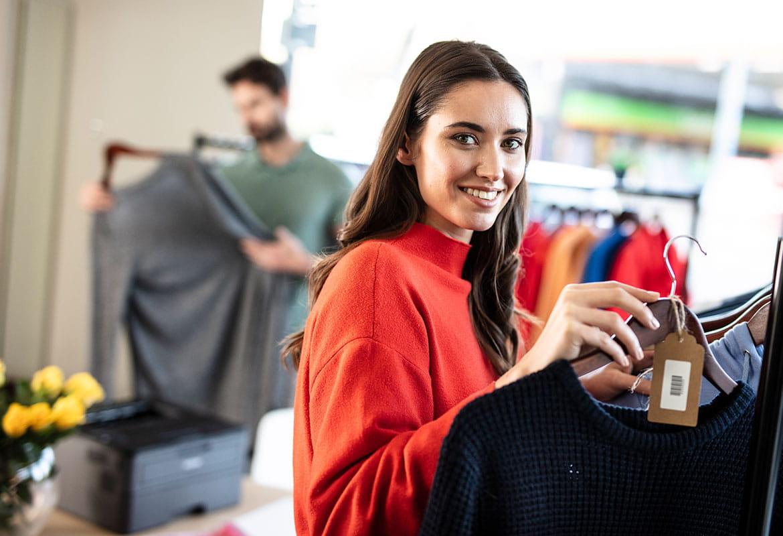 Clienți în magazin de haine cu imprimantă Brother pe birou