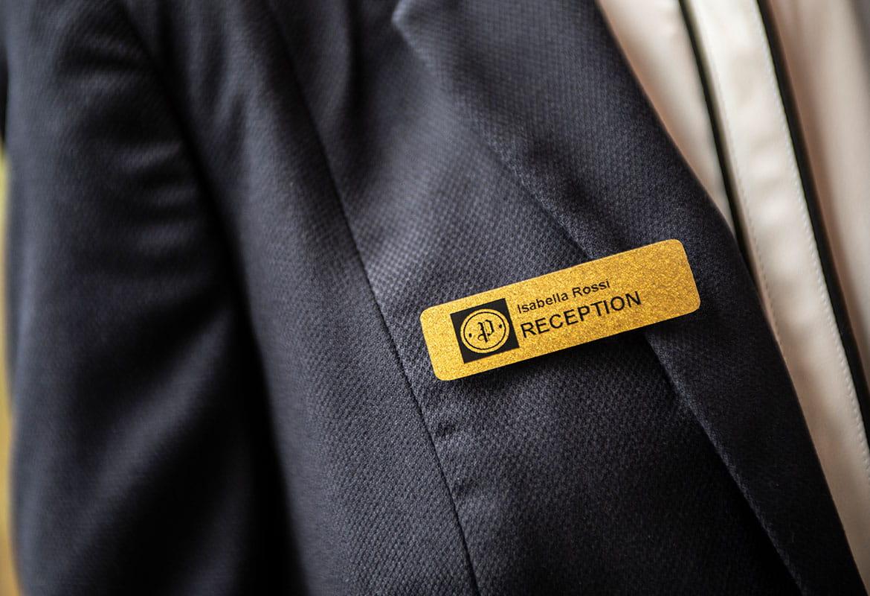 Ecuson auriu de identificare angajați pe sacou gri