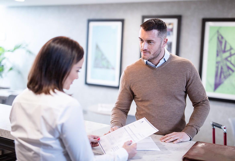 Angajată în spatele biroului de servicii clienți consultând un document