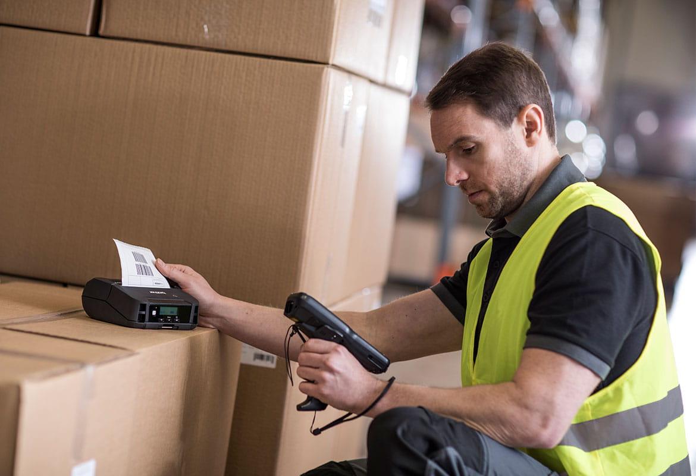 Angajat cu scaner imprimând etichete pe cutii în depozit