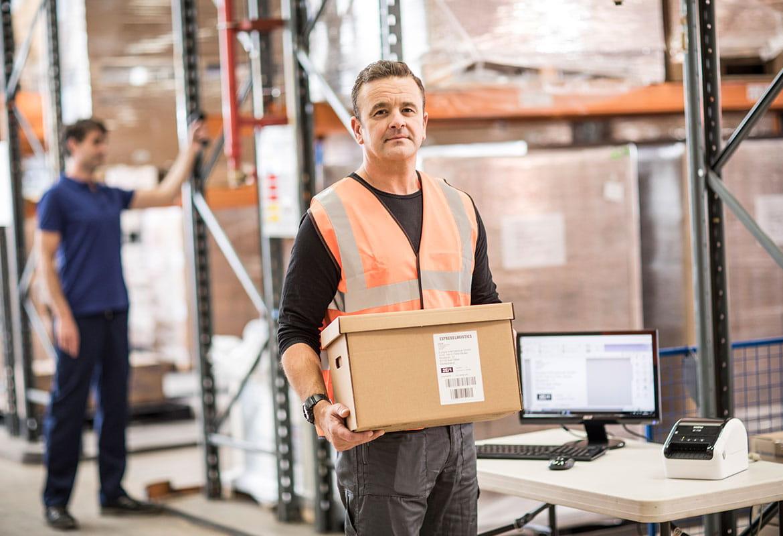 Angajat în depozit cu imprimantă de etichete pe birou
