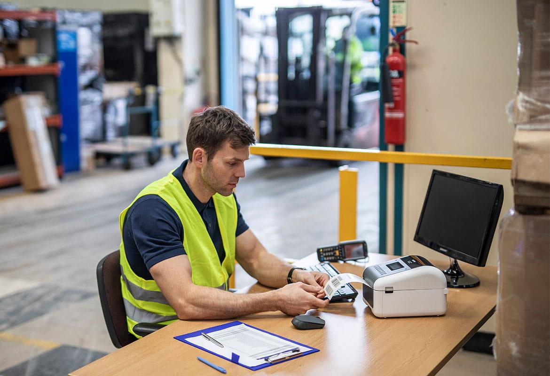Angajat cu vestă galbenă la birou cu imprimantă de etichete Brother TD