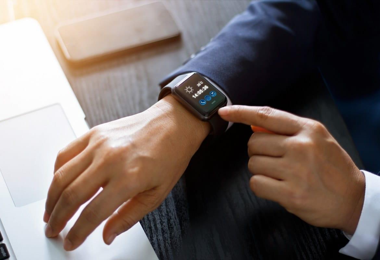 Bărbat în costum folosind un smartwatch la locul de muncă al viitorului.