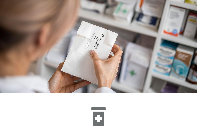 Farmacistă aplicând etichetă în farmacie