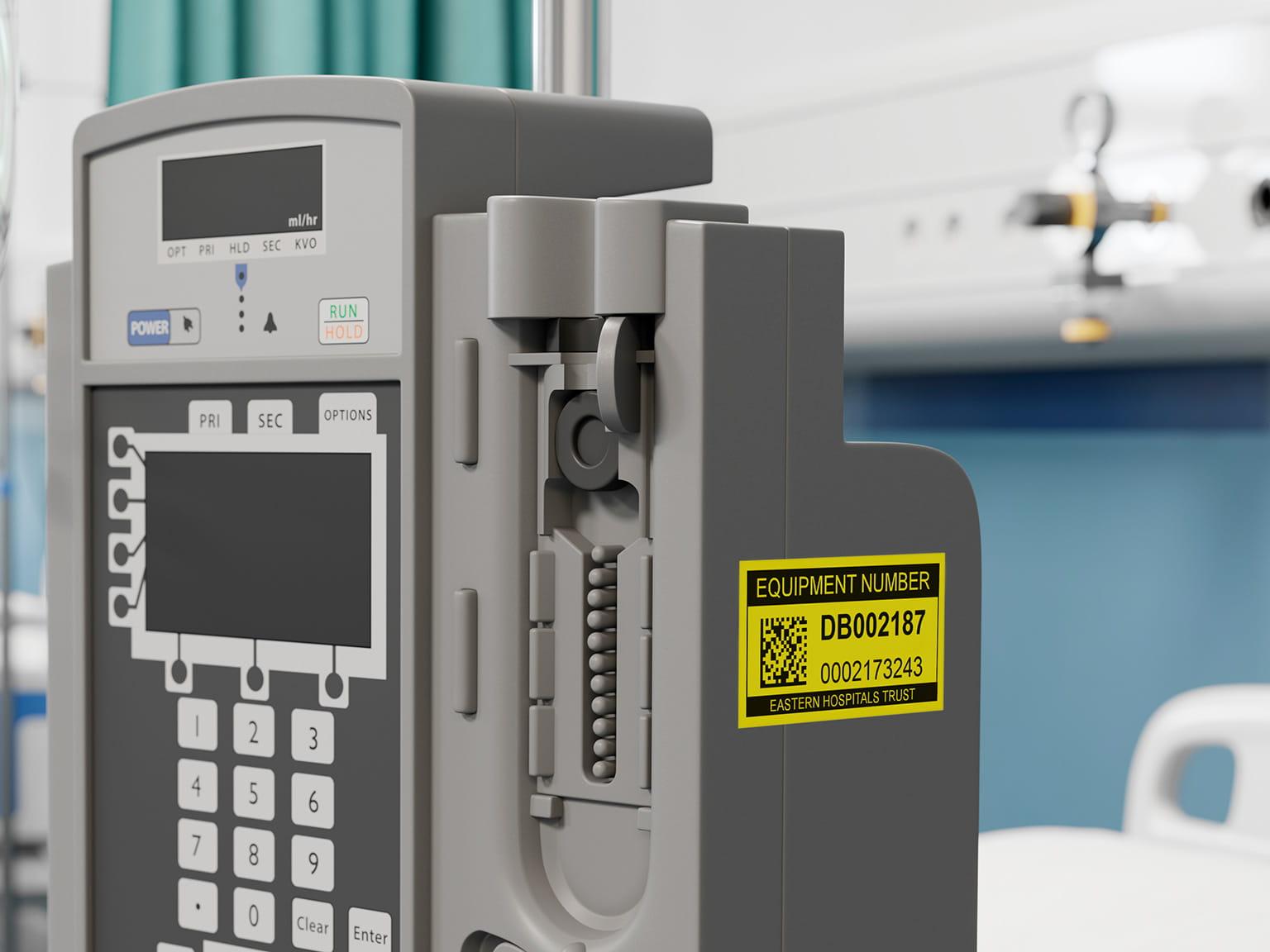 Etichetă de inventar Brother P-touch negru pe galben pe echipament medical