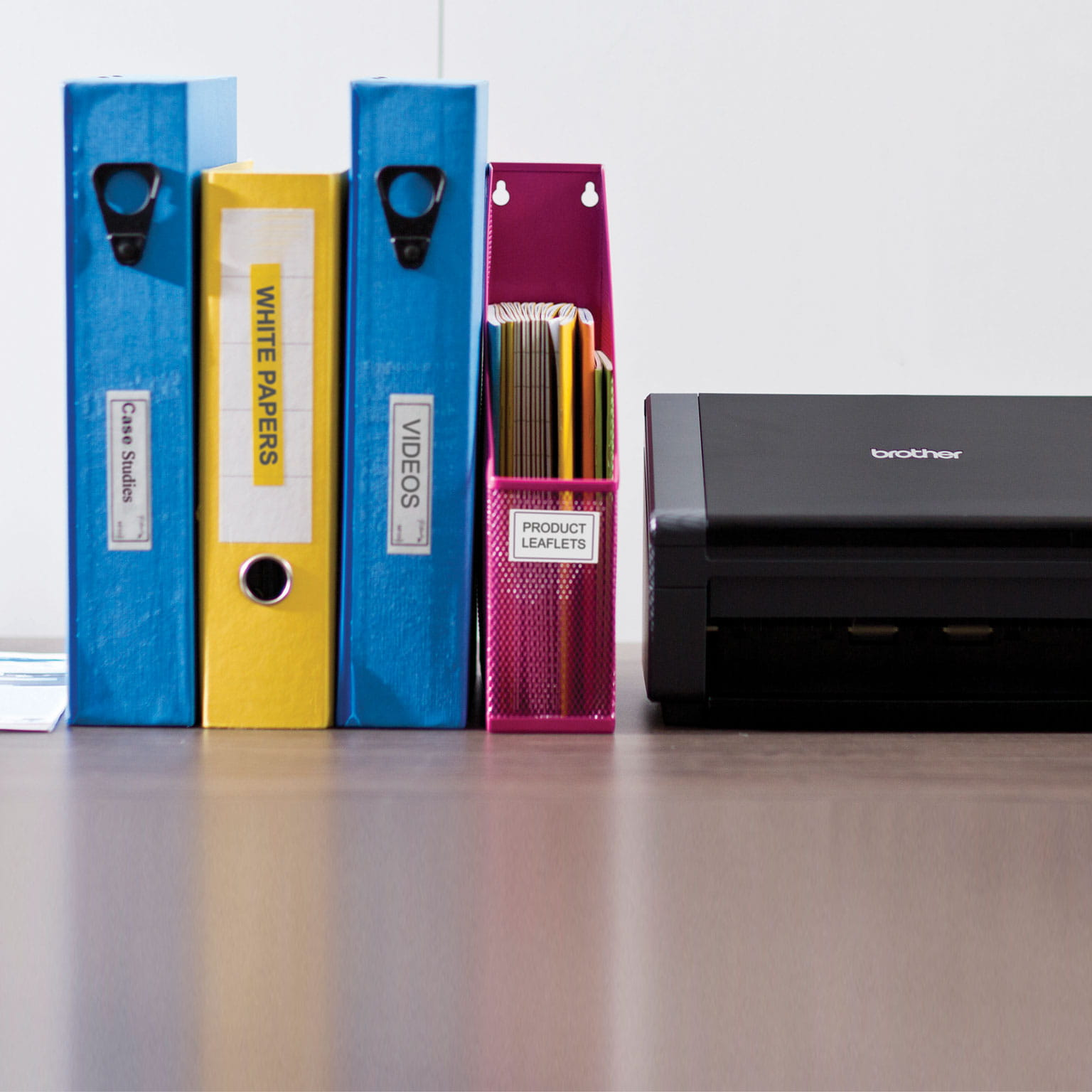 4 different colours folders standing next to a black brother printer