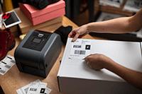 Imprimantă de etichete TD-4T și etichetă de livrare aplicată pe cutie