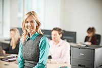 Business woman with blonde hair sitting on a desk with brother printer next to her