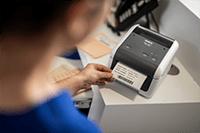 Asistenta imprimand etichete pentru pacienti pe imprimanta de etichete Brother TD-4420DN